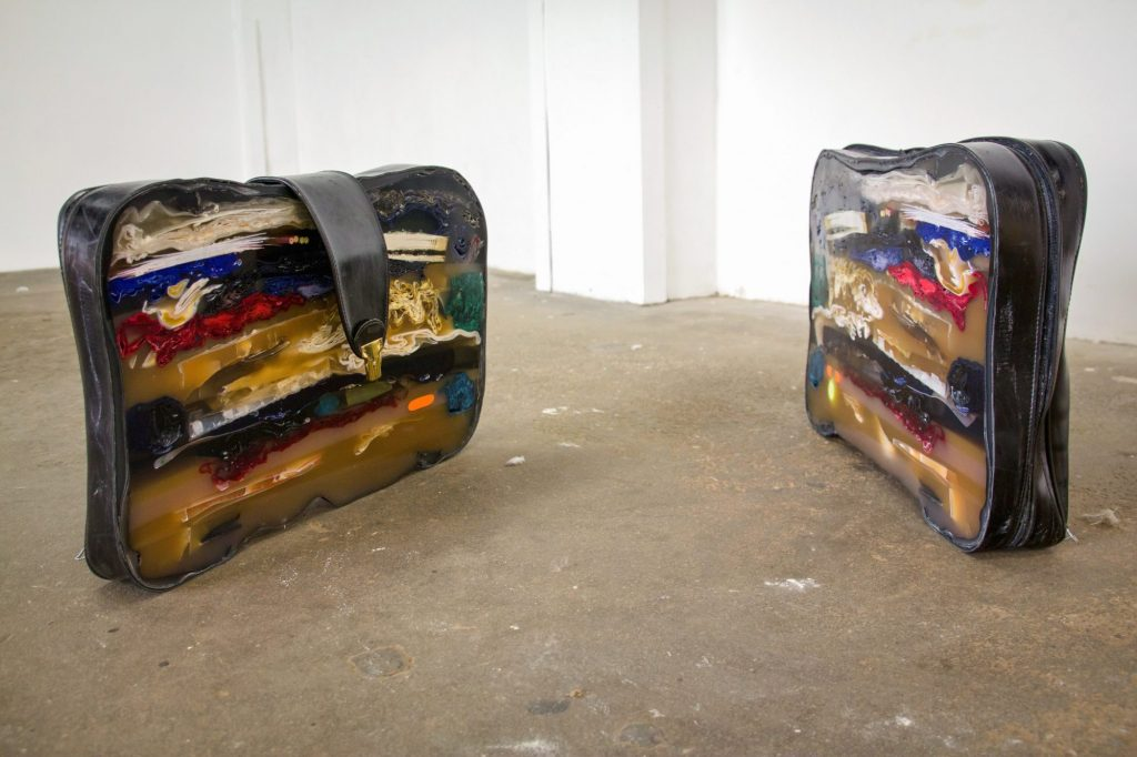 a sculpture of a suitcase cut in two and encased in resin