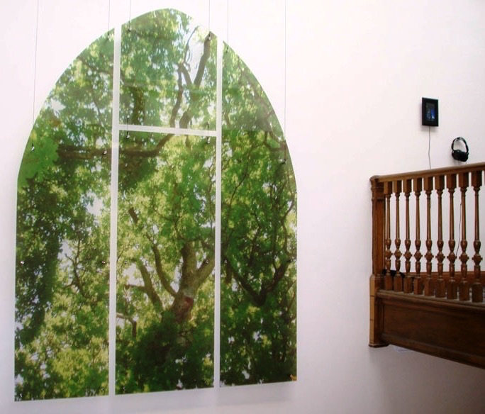 A 2D wall mounted artwork, printed image of trees in a forrest, in the shape of a church window