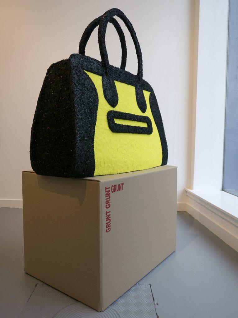 an oversized black and florescent yellow handbag