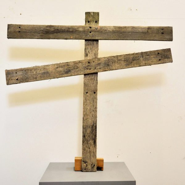 a wooden crucifix form sculpture with two horizontal axis