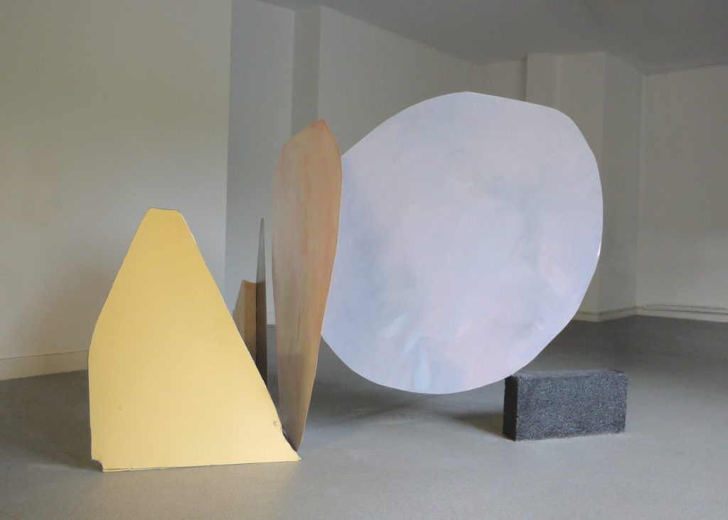 A sculpture made from 3 2D coloured wooden shapes balancing in a space