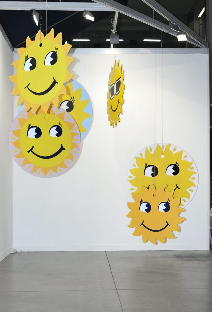 several brightly coloured hanging discs with smiley faces, based on common car air freshener designs