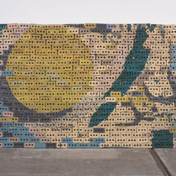 Image shows a sculpture made of several hundred glazed ceramic bricks to make a wall shape against an existing wall