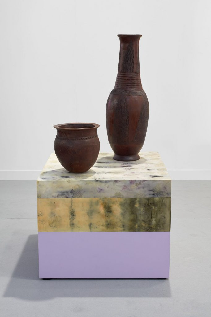 two brown clay vessels ontop of a tye-dyed fabric covered plinth. Yellow and lilac