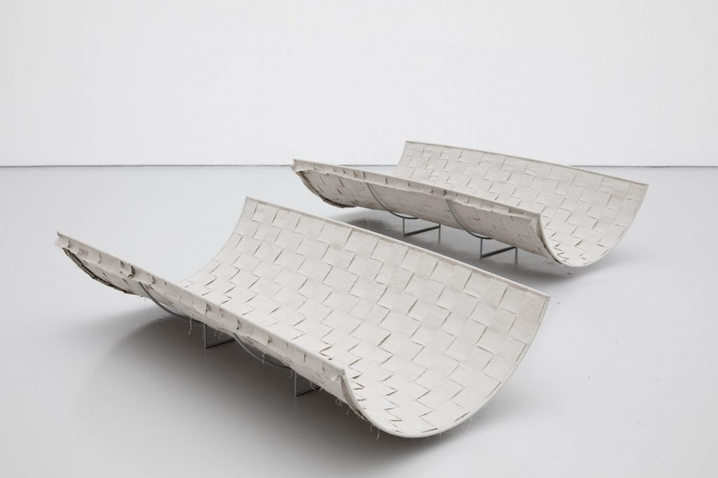 two woven fabric and steel structures on the floor, loosely resembling benches