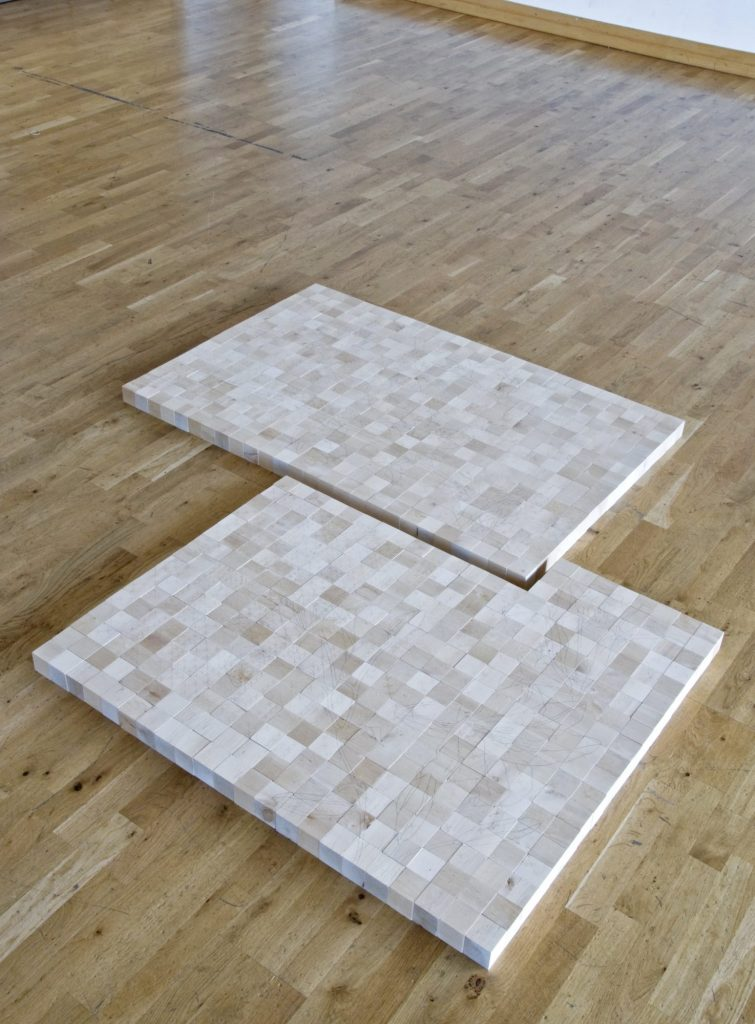 a floor based sculpture made of 2 interlocked squares comprising small wooden bricks