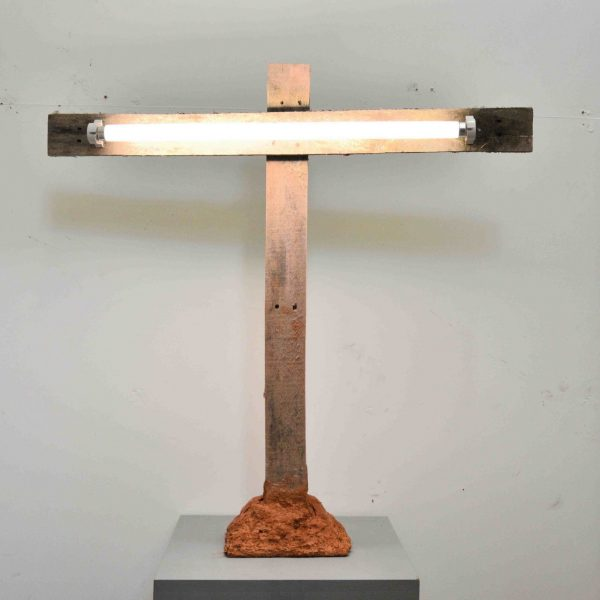 a wooden sculpture of a crucifix form with a florescent light on the horizontal axis