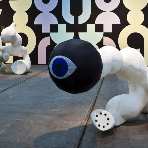 a white plaster sculpture with large black inflatable orb on the top with eye on it