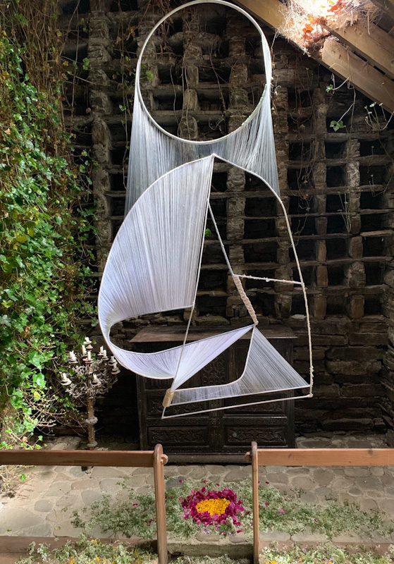 a delicate hanging sculpture with white threads hanging down