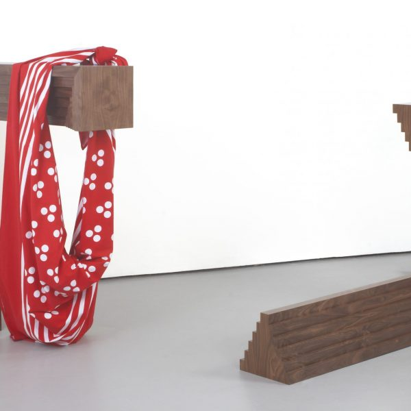 A wooden sculpture in two parts, like ornate right angle corners, one has giant red and white printed handkerchief