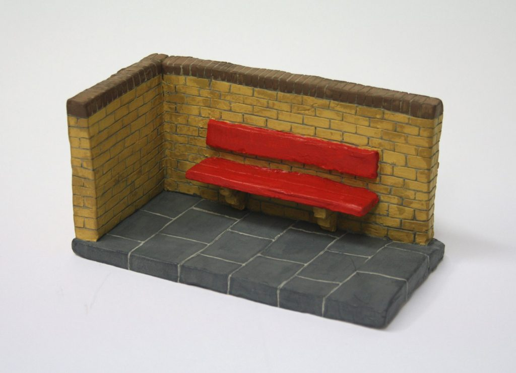 a small clay sculpture of a corner of wall and pavement with a red bench