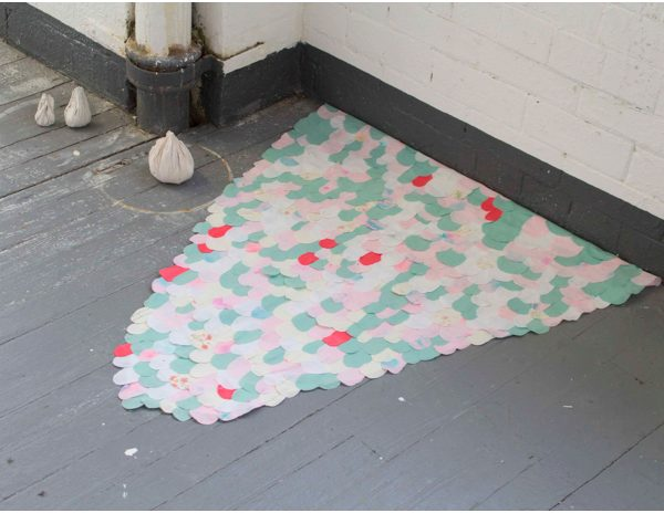 a floor based tongue shaped 2d sculpture made from fabric scales in pink, green and white