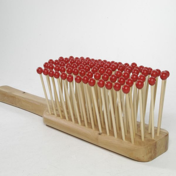 A sculpture of a giant hairbrush made from wooden rods with red golf balls at the tip